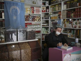 Ahmed Hasim, a member of the Uighur community, takes notes in his grocery store, in Istanbul's Zeytinburnu neighborhood.