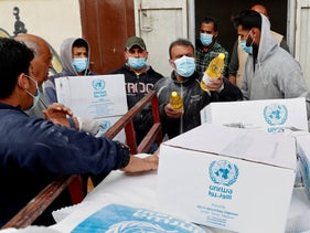 Palestinian workers load food supplies distributed by UNRWA in Gaza City in March.