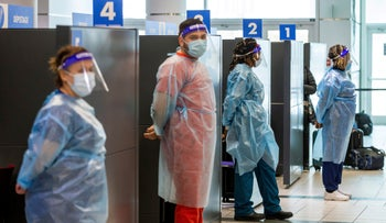 Healthcare workers prepare to test passengers as they arrive at Toronto's Pearson airport after mandatory coronavirus testing took effect for international arrivals this month.