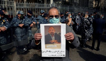 A protester holds a picture of Lokman Slim during a demonstration in Beirut on Thursday. The Arabic words on poster read 'Hezbollah's arms against who? Weapons of terrorism.'