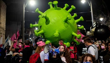 Protesters in Jerusalem carry a coronavirus inflatable at a demonstration against the government's lockdown measures on Saturday.