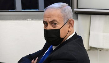 Netanyahu looks on before the start of a hearing in his corruption trial at Jerusalem's District Court on Monday