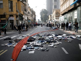 FILE PHOTO: Fabric and clothes are seen on the street during a demonstration by business owners and employees against COVID-19 restrictions, in Tel Aviv