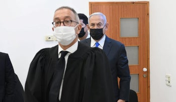 Netanyahu nestled between his attorneys Boaz Ben Zur and Amit Hadad at the Jerusalem District Court on Monday
