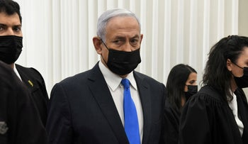 Israeli Prime Minister Benjamin Netanyahu wears a protective face mask as he stands inside the courtroom just before the start of a hearing in his corruption trial at Jerusalem's District Court February 8, 2021.