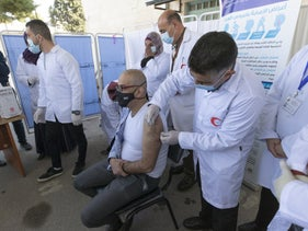 A medic administering a Moderna COVID-19 vaccine to a fellow medic in the West Bank city of Bethlehem last week.