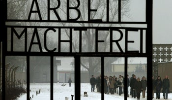 Visitors walk past the main gate of the former Nazi concentration camp in Oranienburg-Sachsenhausen north of the German capital Berlin in 2004.