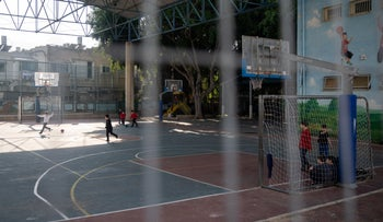 Children play by a closed school in Givatayim, last month.