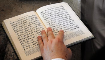A person reads a Hebrew-language Bible.