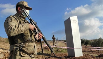 Turkish police officers guard a monolith, found on an open field near Sanliurfa, southeastern Turkey.