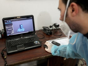 A physiotherapist works on a laptop as he designs 3D transparent face mask for Palestinian boy Ahmed Al-Deeb in Gaza City.