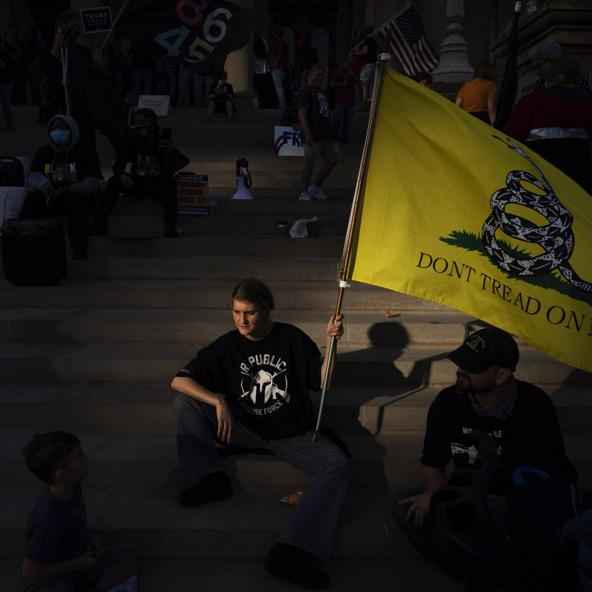 "A Trump supporter sits on the steps of the State Capitol with her family as a protest against the presidential election results winds down in Lansing, Michigan in November. She's holding a flag that says ""Do not tread on me"""