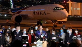 Lebanon's caretaker health minister Hamad Hasan talks near the aircraft carrying doses of the Pfizer/BioNTech vaccine at Beirut International Airport, Lebanon, today.