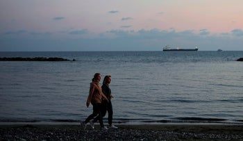 Women walk at the beach during sunset in southern coastal city of Limassol, Cyprus, in December.