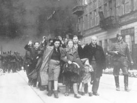 A group of Polish Jews are led away for deportation by German SS soldiers during the destruction of the Warsaw Ghetto by German troops after an uprising in the Jewish quarter in 1943.