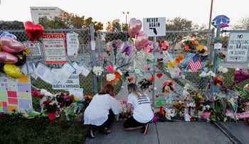 People light candles at a makeshift memorial outside Marjory Stoneman Douglas High School in 2018.