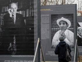A visitor looks at portraits of Holocaust survivors in the exhibition in Germany