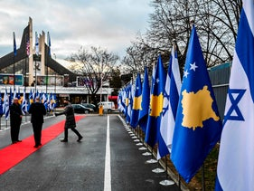 Kosovo Albanians walk past the flags of Israel and Kosovo flag at the Foreign Ministry headquarters in Pristina displayed during a Zoom ceremony establishing diplomatic relations