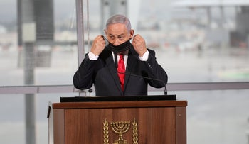 Netanyahu removes his mask to make a speech at Ben Gurion Airport in December.