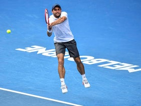Russia's Aslan Karatsev hits a return against Bulgaria's Grigor Dimitrov during their men's singles quarter-final match on day nine of the Australian Open tennis tournament in Melbourne