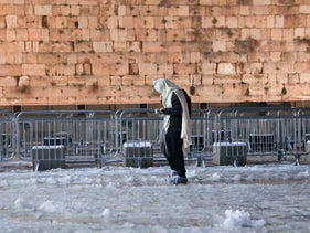 A man praying in the snow at the Western Wall this morning.