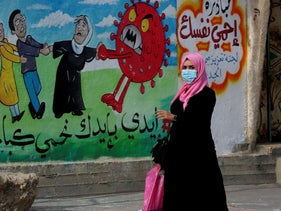 A woman walking past a mural in Gaza, last year.
