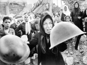 A Palestinian woman with helmets she said were worn by perpetrators of the Sabra and Chatila massacre, at a memorial service in Beirut for its victims, September 27, 1982.