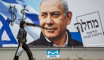 A defaced campaign poster shows Benjamin Netanyahu with a spray-painted cigar, in 2019.