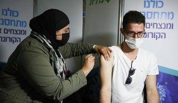 A woman administers a COVID-19 vaccine to a patient in Jerusalem, earlier this month.