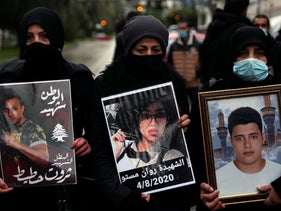 Relatives of victims of the Beirut port explosion hold portraits of their loved one who were killed during the explosion, outside Lebanon's Justice Palace, today.