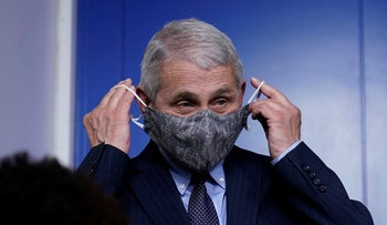Dr. Anthony Fauci putting his face mask back on after speaking with reporters at the White House last month.