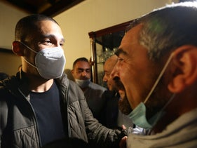 Algerian journalist Khaled Drareni, left, meets with relative after being released from prison in Algiers.