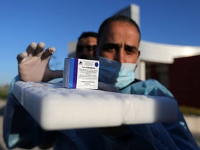 A Palestinian health worker displays a box of Russia's Sputnik V vaccine sent by United Arab Emirates at Rafah crossing in the southern Gaza Strip today.
