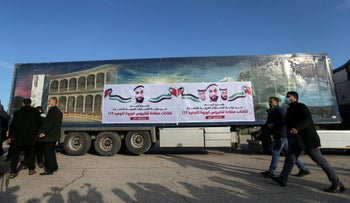 Palestinians walk past a truck carrying a shipment of Russia's Sputnik V vaccine sent by United Arab Emirates, at Rafah crossing in the southern Gaza Strip today.