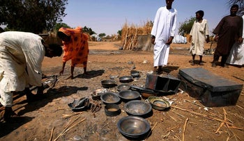 Residents of a village in the southern part of Sudan looking at huts and dishes burned by government militias, February 2021