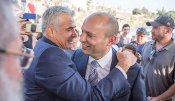 Bennet and Lapid share a rare embrace.