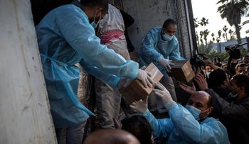 Palestinian workers unload a truck from 20,000 doses of Russian-made Sputnik V vaccine upon its arrival to Gaza Strip, yesterday