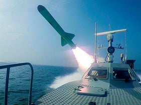 An Iranian Revolutionary Guard's speed boat fires a missile during a military exercise