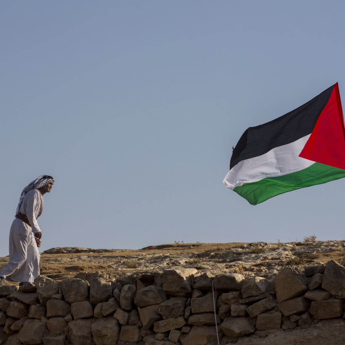 A Palestinian man walking toward the Palestinian flag in the South Hebron Hills in the West Bank.