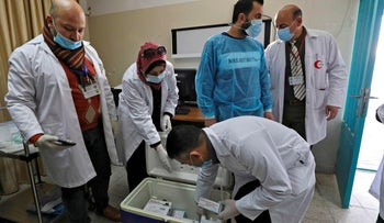 A Palestinian health worker takes out a box of Moderna COVID-19 vaccine provided by Israel in the biblical West Bank city of Bethlehem,