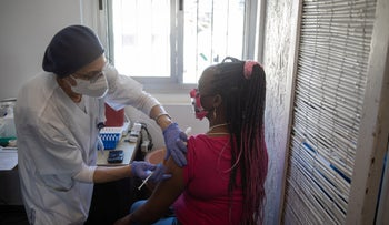 A woman receives her COVID-19 vaccine at a center for Israel's foreign workers and asylum seekers.