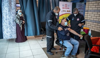 MDA workers vaccinating Palestinians at the Qalandiya crossing in the West Bank, earlier this month.