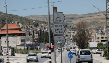 Signs pointing to Yitzhar in the nearby Palestinian town of Huwara in 2019.