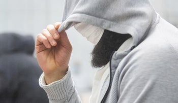 A man who calls himself Abu Walaa hides his face at the Higher Regional Court in Celle, Germany.