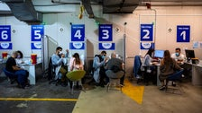 Israelis receive a Pfizer-BioNTech COVID-19 vaccine from medical professionals at a coronavirus vaccination center set up on a shopping mall parking lot in Givatayim, Israel