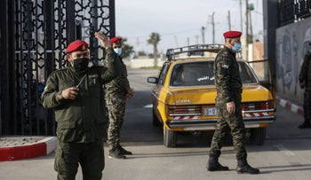 Members of the Palestinian security forces loyal to Hamas, mask-clad due to the coronavirus pandemic, stand guard at the Rafah border crossing with Egypt,