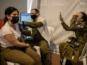 An Israeli soldier receives a COVID-19 vaccine at an army base in central Israel, in early February.