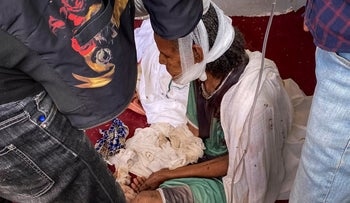 An older woman who fled to Axum in the Tigray region of Ethiopia, sits with her head bandaged after sustaining injuries in an attack there, before dying of her injuries days later in November