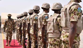 Nigerian soldiers stand on attention at a base in January