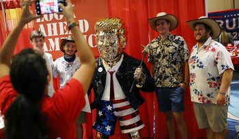 People take a picture with former President Donald Trump's statue on display at the Conservative Political Action Conference held in the Hyatt Regency in Orlando, Florida
